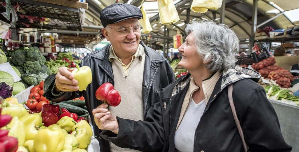 Smiling senior couple buying vegetables together at a farmer's market.