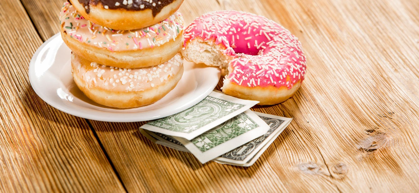 Three donuts stacked on a plate on top of money.