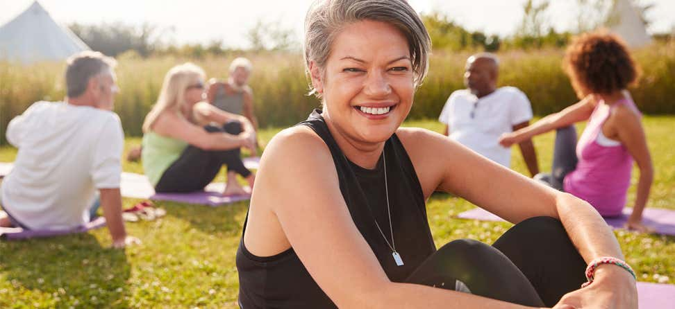 A Black senior woman smiles at the camera while at a yoga retreat with other older adults.