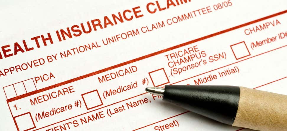 Close up shot of a Medicare health insurance claim form and a pen.