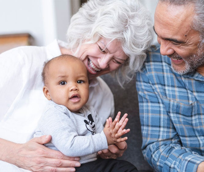 An interracial senior couple is playing with their grandson in their living room.