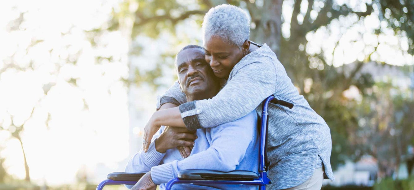 A Black senior woman embraces her husband who's sitting in a wheelchair. They're enjoying the beautiful day outside.