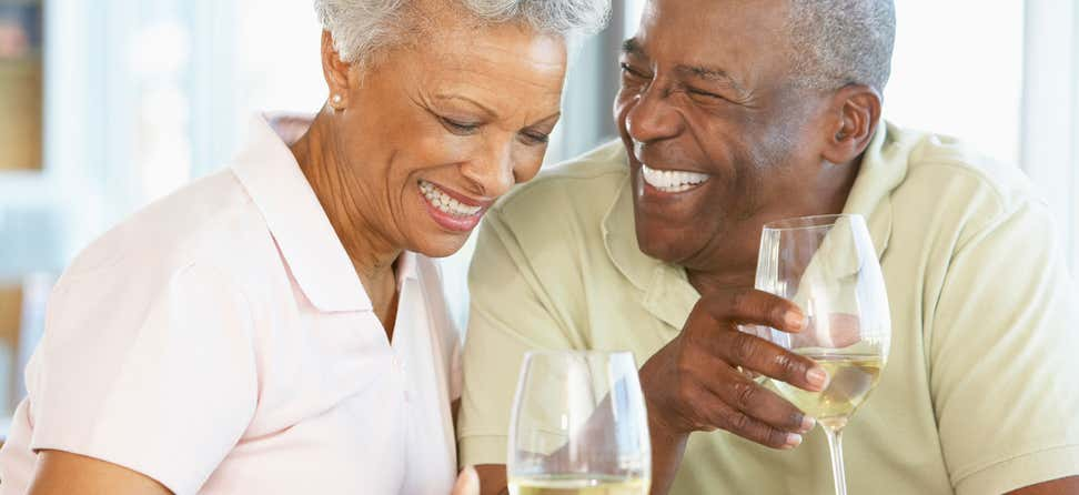 A senior African American couple are laughing while enjoying their wine.
