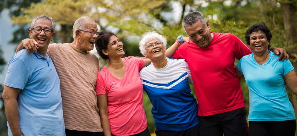 Un grupo de personas mayores diversas están afuera, disfrutando de la compañía del otro mientras se ríen.