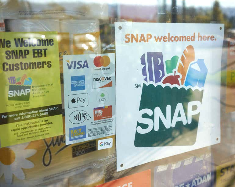 Close up of a SNAP sign on the window of grocery store.