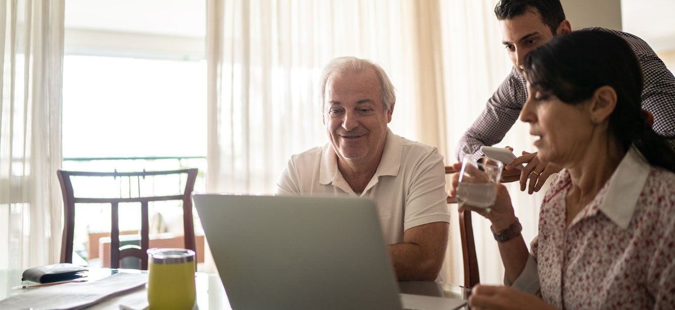 An older Hispanic couple, alongside their son, are looking at a computer, discussing their financial situation together.