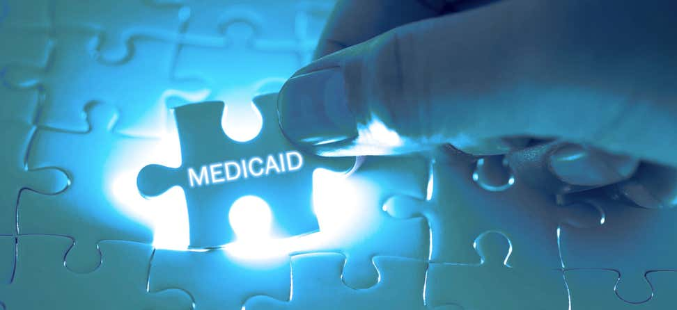"A doctor holds a missing puzzle piece above a large puzzle that says ""Medicaid""."