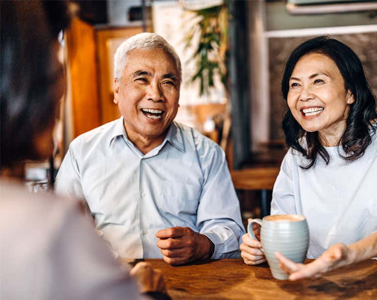 An Asian senior couple is sitting down having coffee is a coffee shop with their caregiver, loved one.