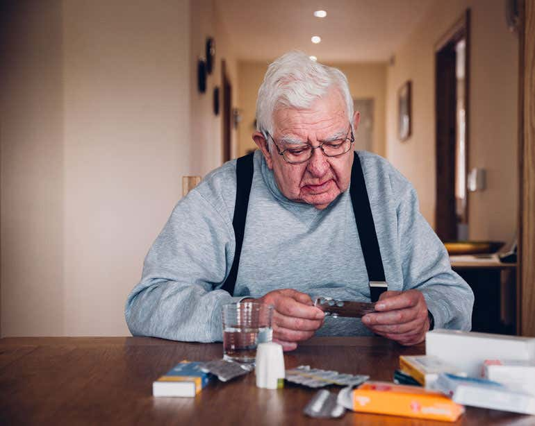 A senior man is sitting as his dining room table with all of his prescriptions.