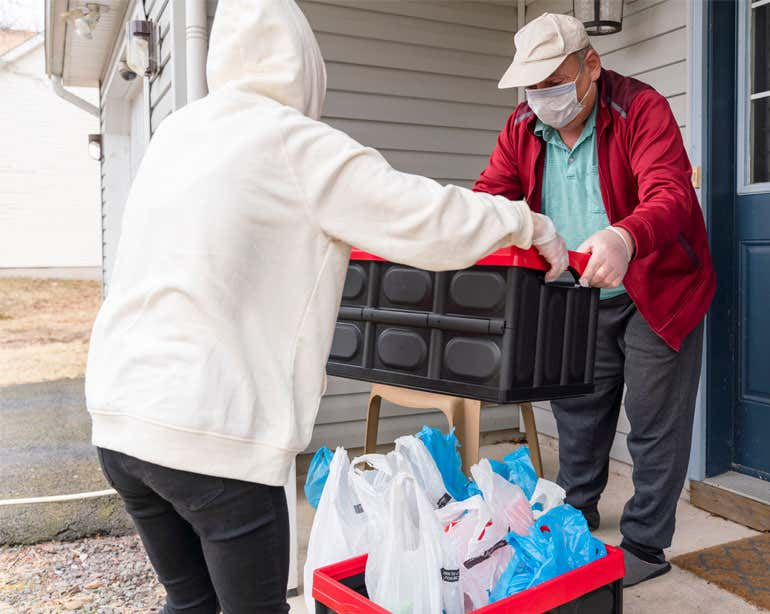 An older man is receiving a grocery delivery at home during the pandemic and is wearing a mask.