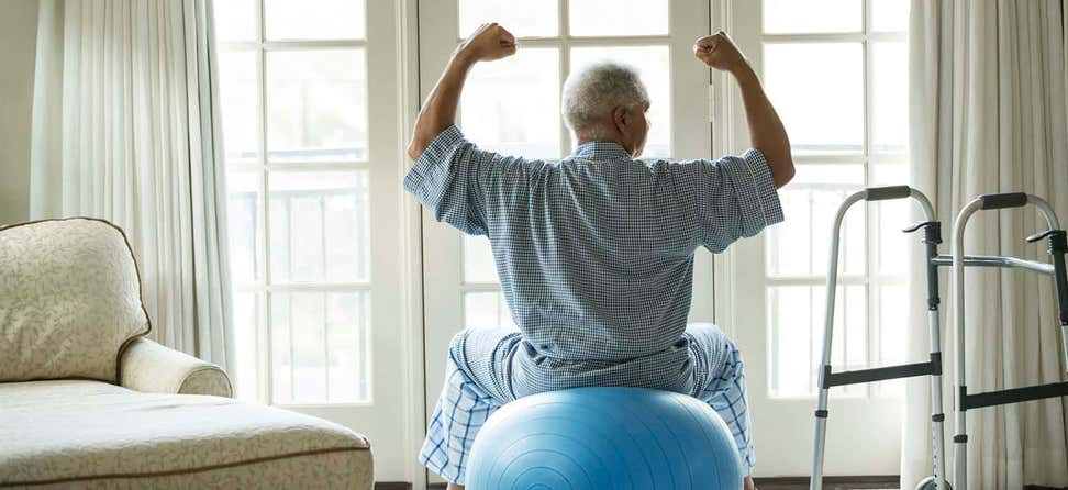 Senior African American man sits on a fitness ball at home while holding his arms up to show his strength.