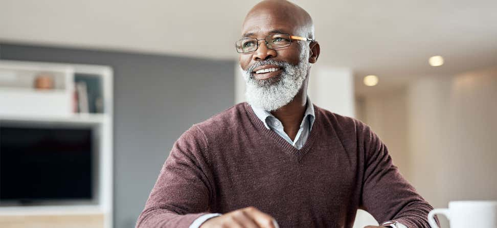 A senior black man is smiling, looking away from the camera, thinking about his financial planning choices.