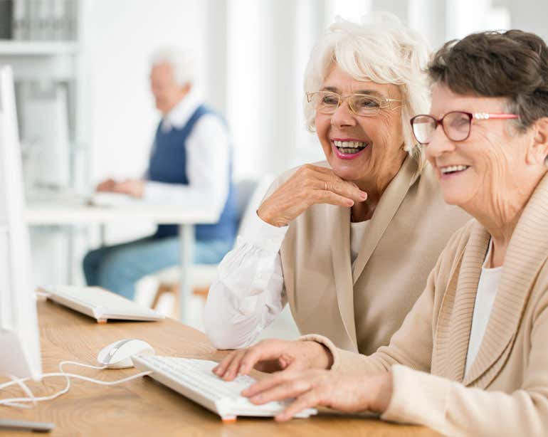 Two senior women are working at a computer together, smiling. There's an older man seen in the foreground also on a computer.