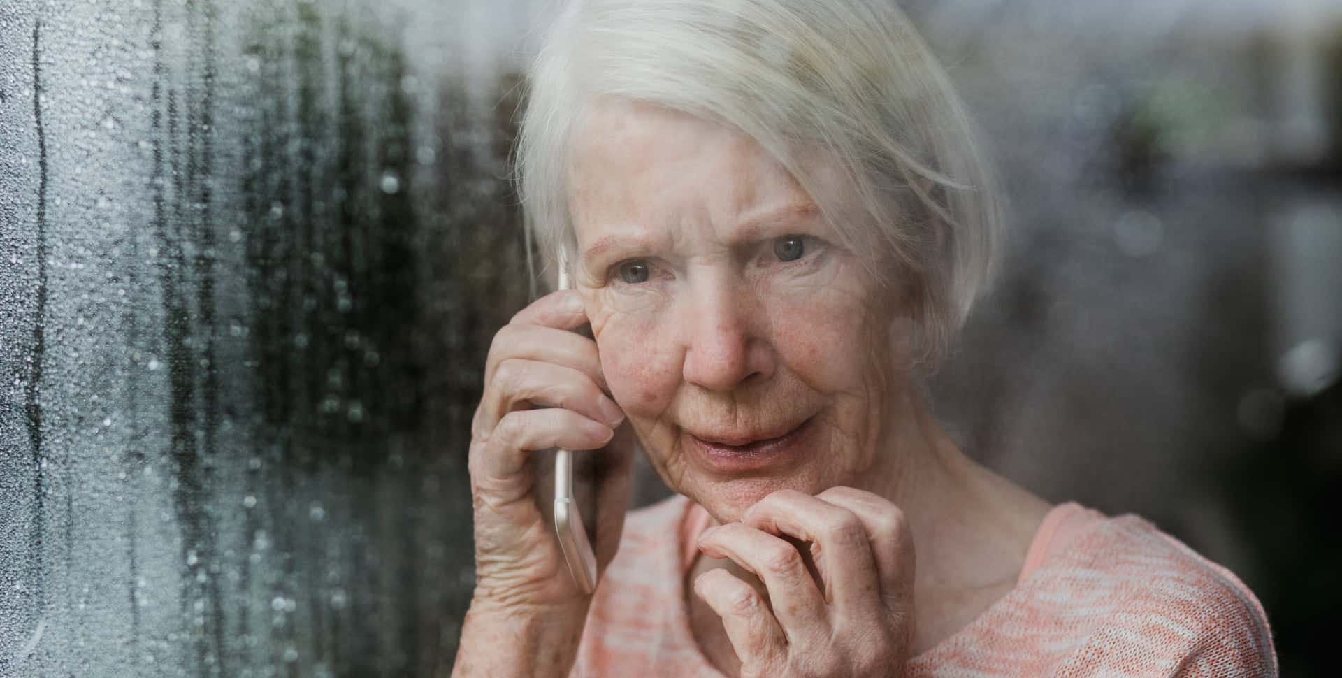 Older woman looking out window at storm while on cell phone with worried expression