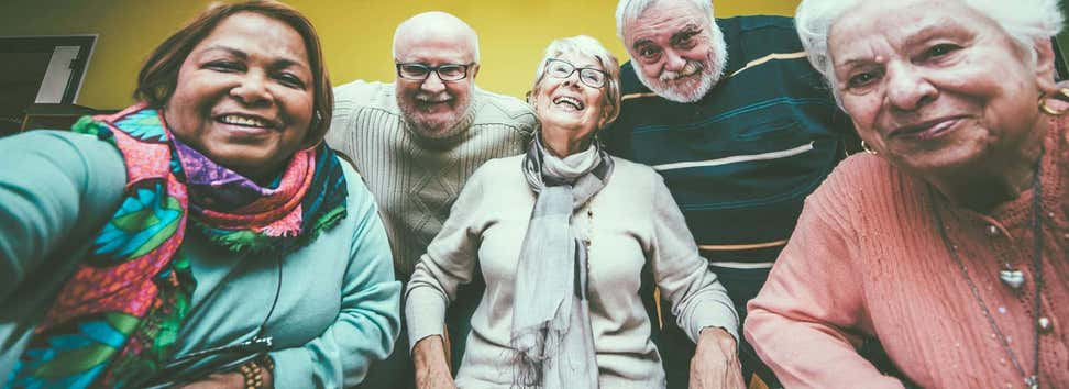 A group of multi-ethnic seniors pose for the camera at a senior center.