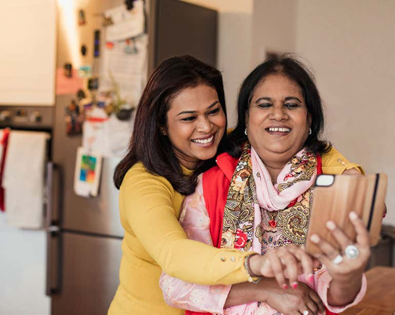 A senior Bangladeshi woman is being hugged by her daughter while they're taking a selfie.
