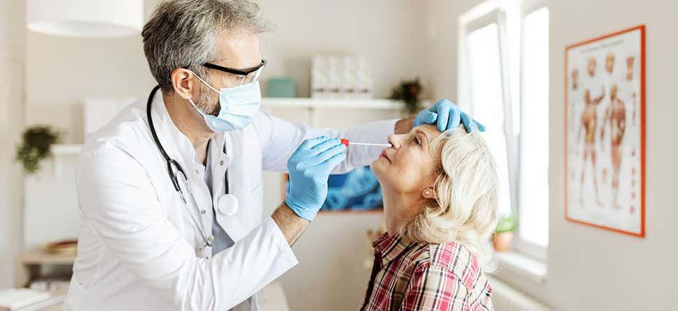 A doctor takes a nasal swab from a senior woman for genetic testing.