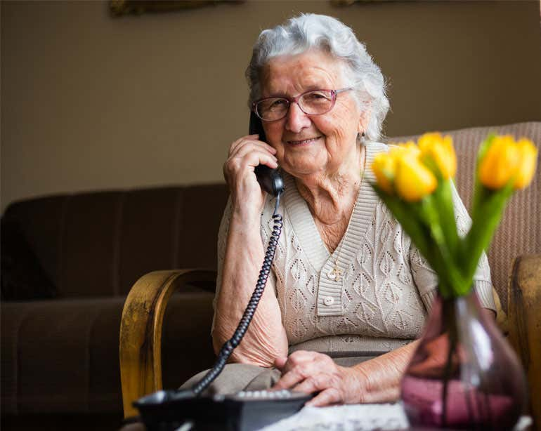 A senior Caucasian woman is smiling while talking on the phone in her home.