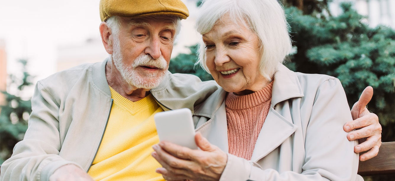 A senior Caucasian couple is sitting on a park bench video calling their child, smiling and enjoying conversation.