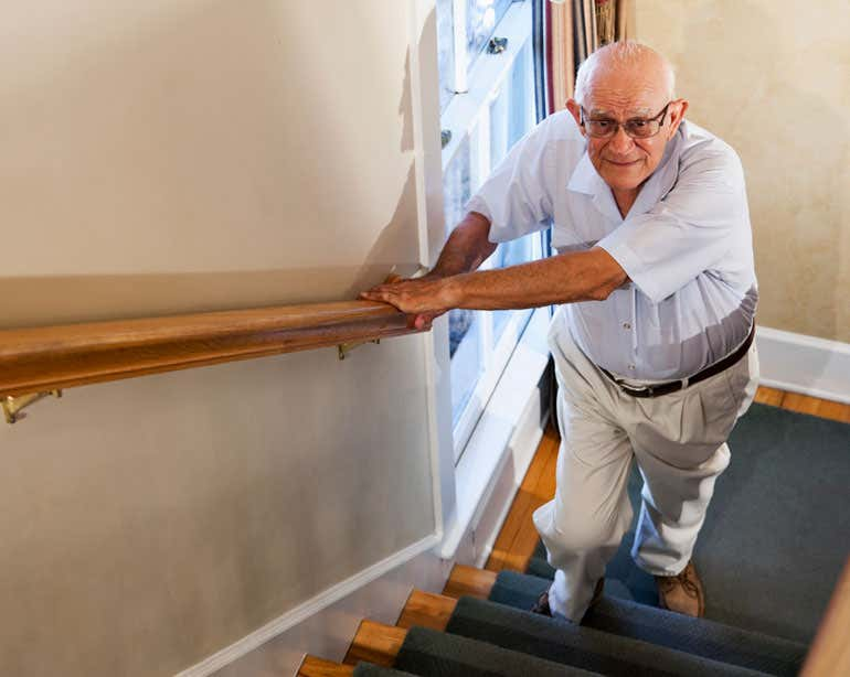 A senior Caucasian man is looking up while he's making an attempt to walk upstairs.