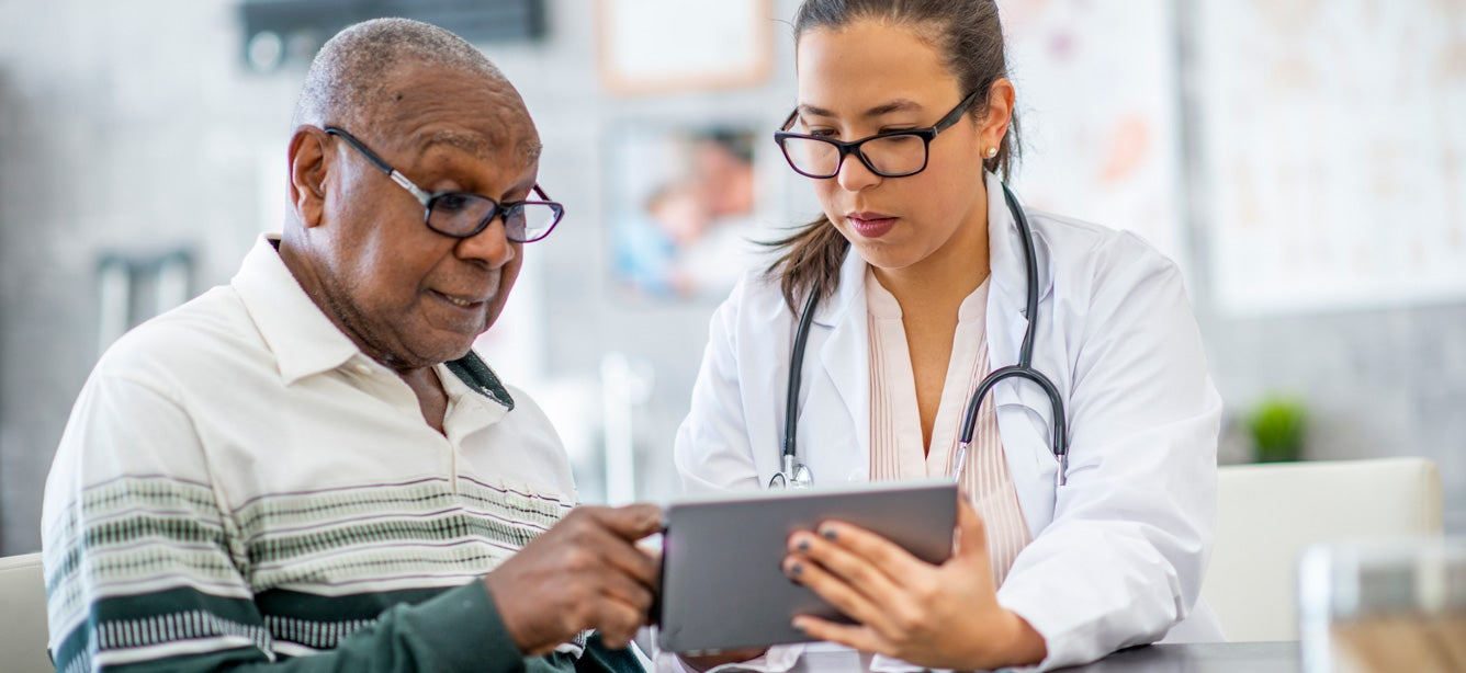 Senior black man consults with doctor using a tablet.