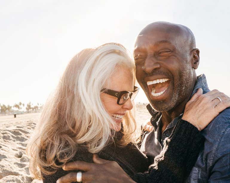 An older interracial couple is seen laughing and embracing at the beach.