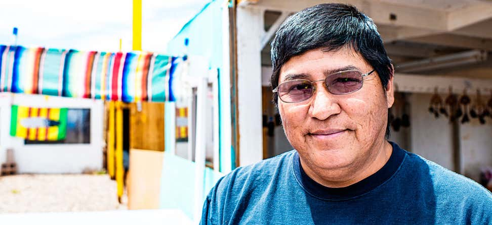A senior Navajo man with sunglasses on poses for the camera outside.