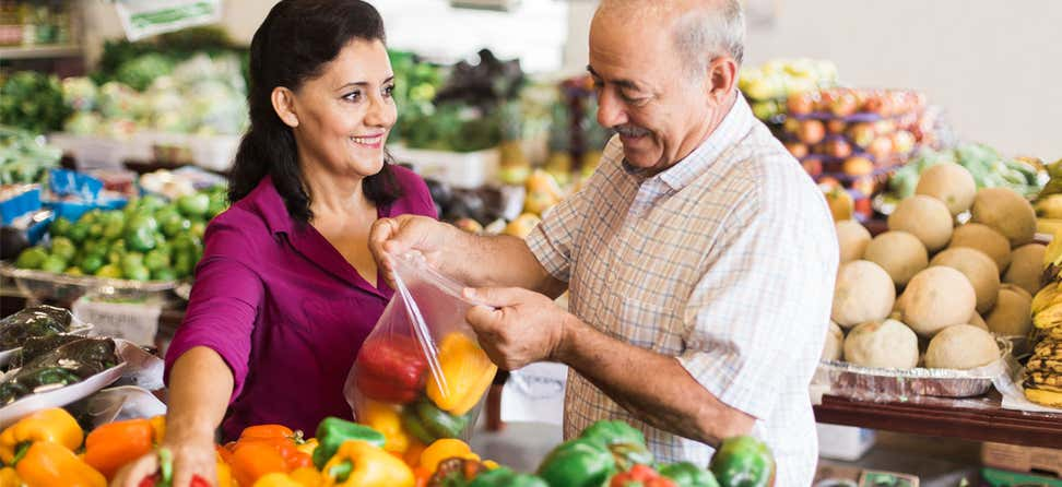 Older Hispanic couple is putting bell peppers into bag at grocery store together.