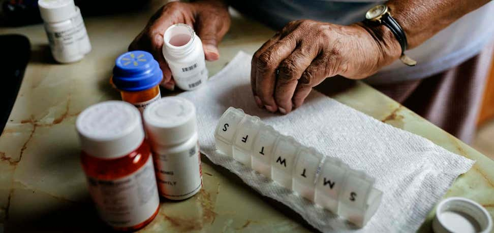 Senior sorts through daily prescriptions and places them into a daily pill container.
