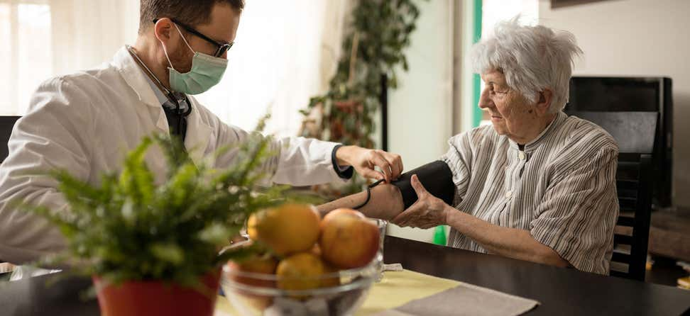 A doctor wearing a face mask adjusts the blood pressure gauge on an older woman during an in-home medical check-up.