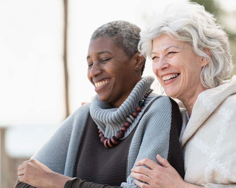 Two senior women, Black and Caucasian, are hugging each other, enjoying the day outside.