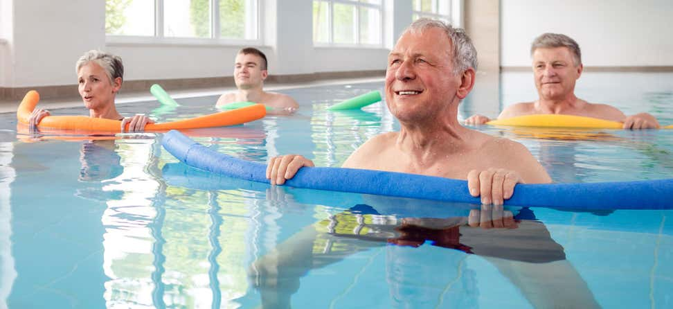 A group of seniors are in a pool doing water aerobics together to improve health and reduce injury.