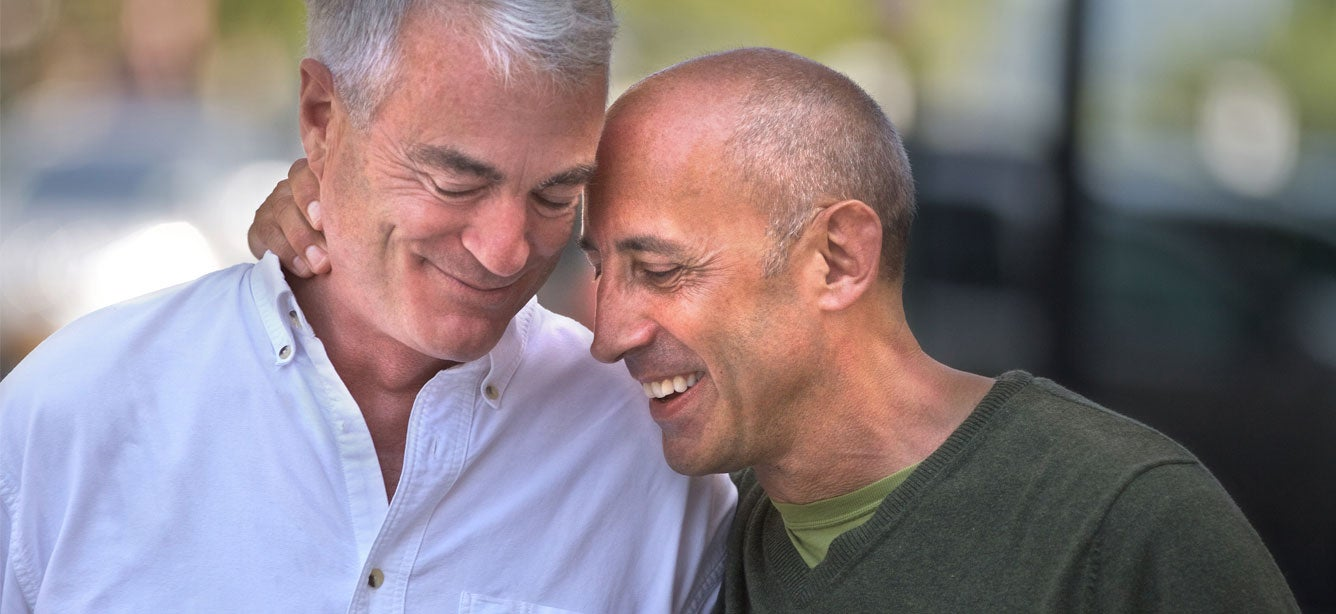 An elderly gay caucasian couple smile while embracing each other.