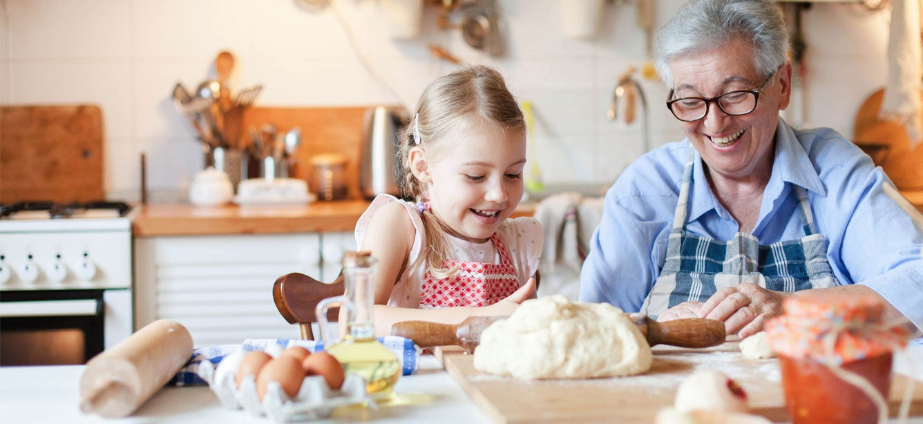A grandmother wearing glasses is in her kitchen making dough with her granddaughter, both are smiling, having fun.