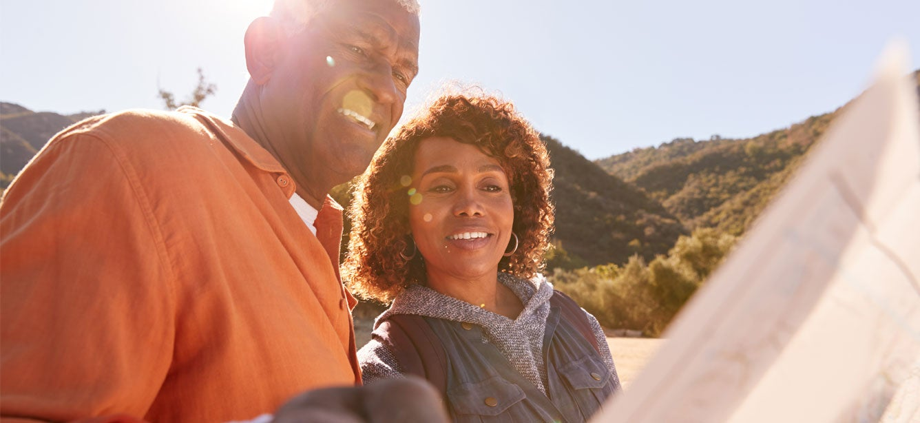 A senior Black man and his daughter are outside enjoying nature, looking at a map.