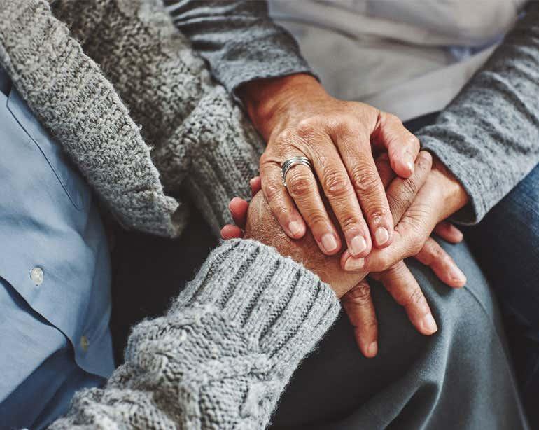 Close up shot of a senior Black couple holding hands.
