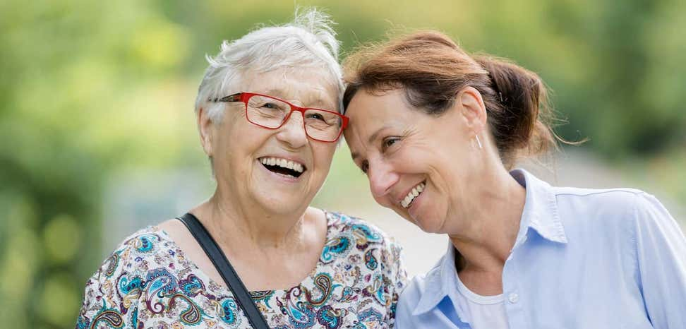 Two happy older women take a walk outside together.