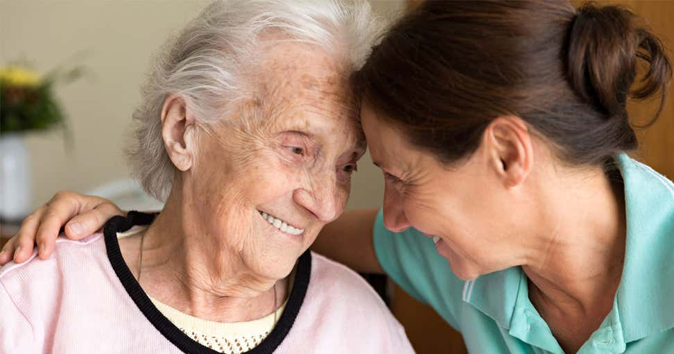 A senior woman smiles, hugging her caregiver during her house visit.