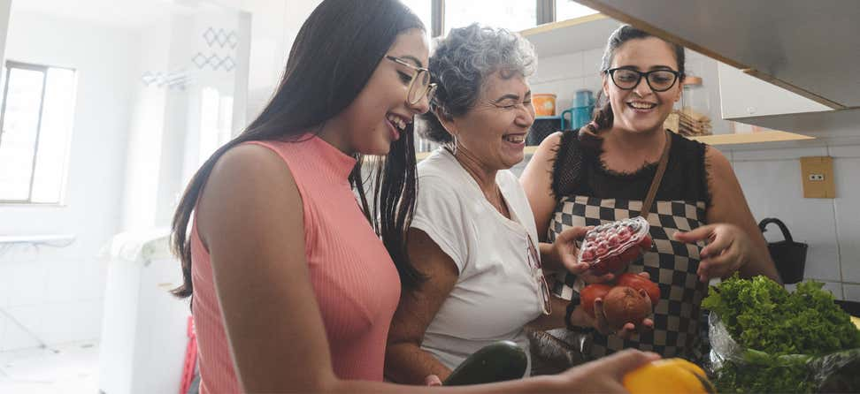 An older hispanic woman unpacks groceries with her daughter and granddaughter in the kitchen.