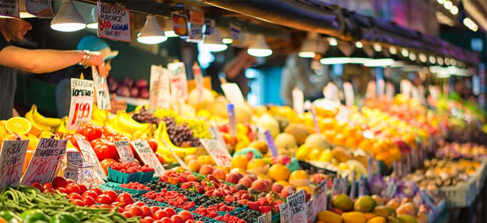 A farmers market stand loaded with fresh fruits and vegetables (Pike Place in downtown Seattle).
