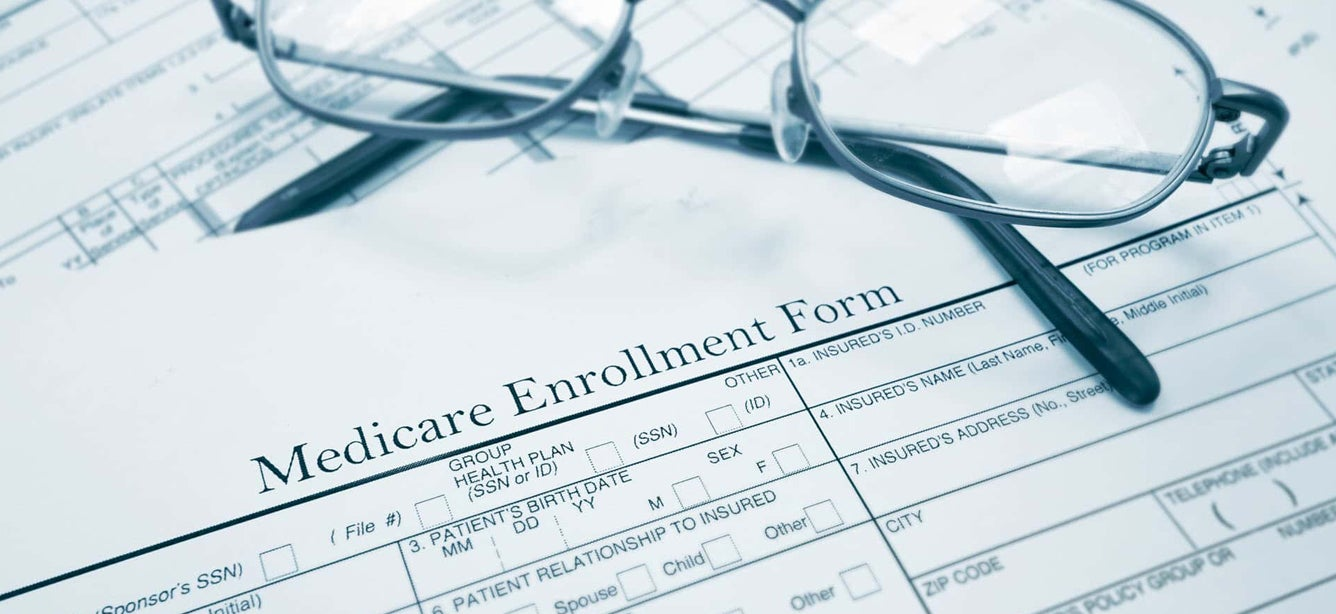 Eyeglasses sit atop a Medicare enrollment form.