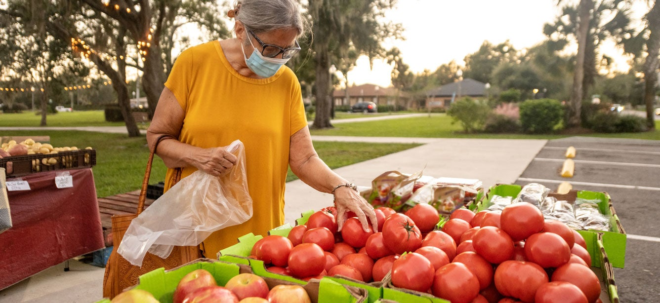 A senior Hispanic woman wearing a mask is shopping at a farmer's market picking out fresh produce.
