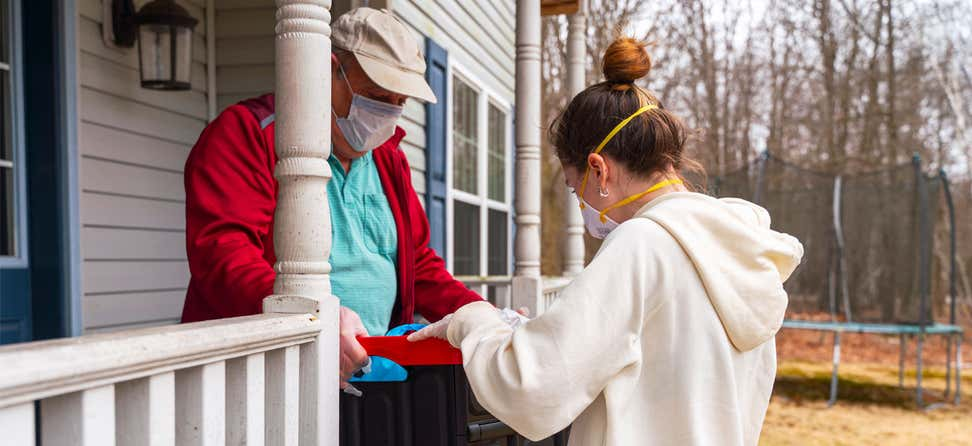 An older man receives a grocery delivery at home during the COVID-19 coronavirus outbreak.