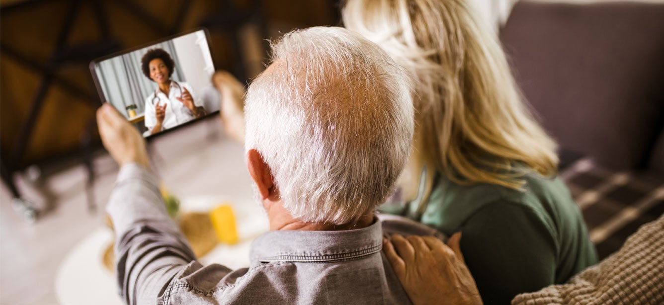 A senior couple is at home holding a tablet during a telehealth call with their family doctor.